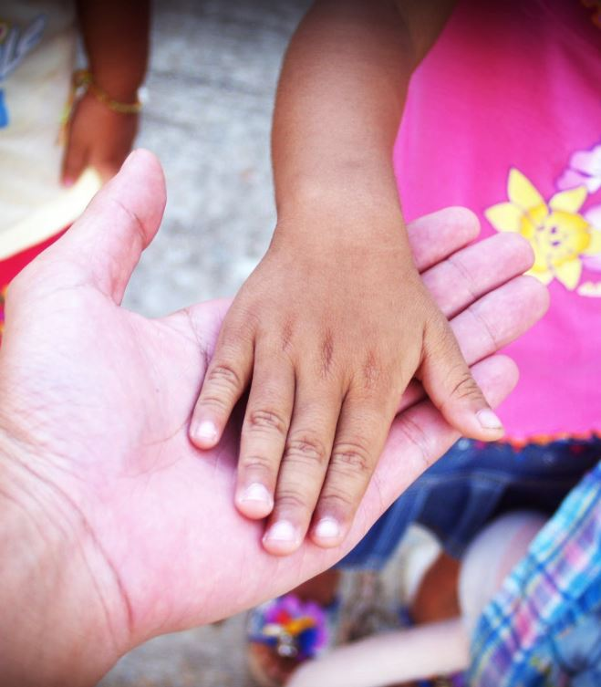 Little girl holding hands with an adult