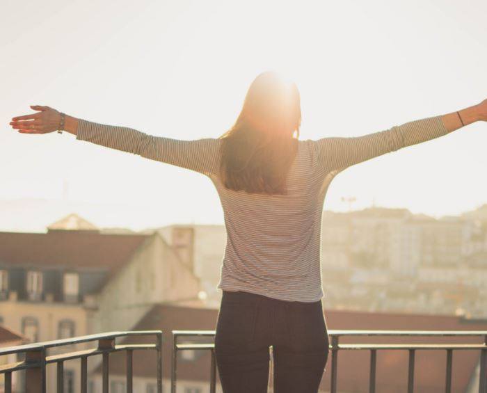 Woman with hands out to her side gazing at the sun