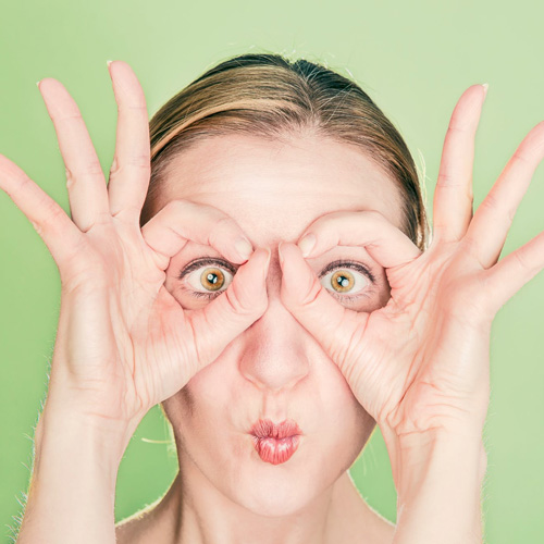 Woman with hands around eyes like glasses